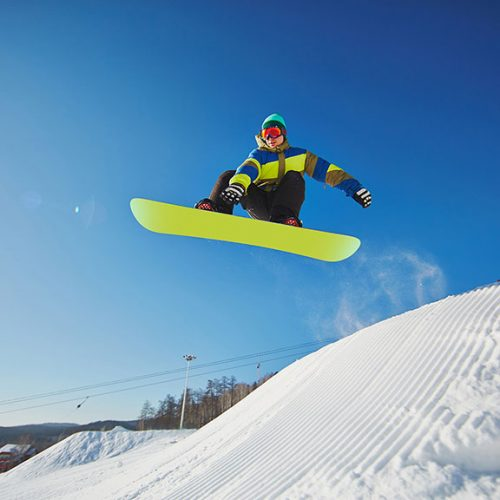 Portrait of young man snowboarding in winter against blue sky